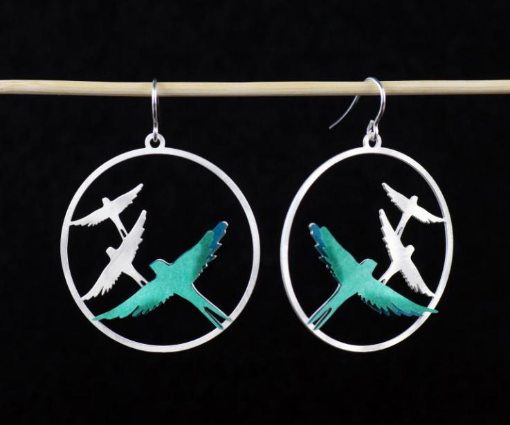 Carved earrings, with silver hook clasps and green paper birds that are set in layers to a circular filigree base.