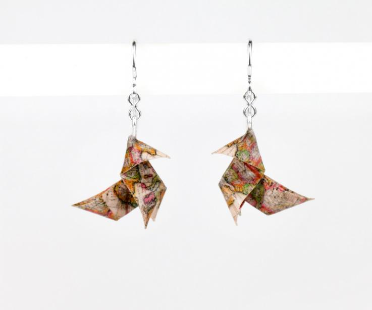 Front view of a pair of silver hooked earrings, topped with two 3D paper origami birds illustrated with old warm tone world maps.