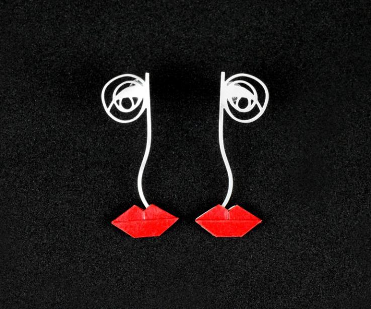 Vista frontal de pendientes largos plateados de estructura y diseño cubista que representa un rostro femenino con engastes de labios de papel rojo.