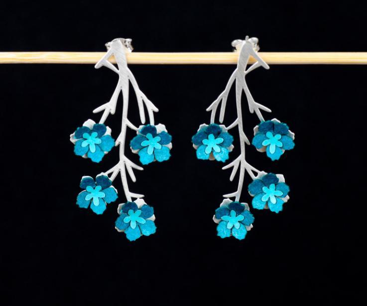 Vista frontal de dos pendientes con cierre oculto, tallados en forma de ramas invertidas con engastes de flores de papel azul reforzado y efecto 3D.