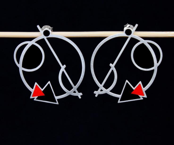 Originales zarcillos circulares plateados, con figuras geométricas superpuestas y remates de color negro y rojo en papel semi brillo sobre fondo negro.