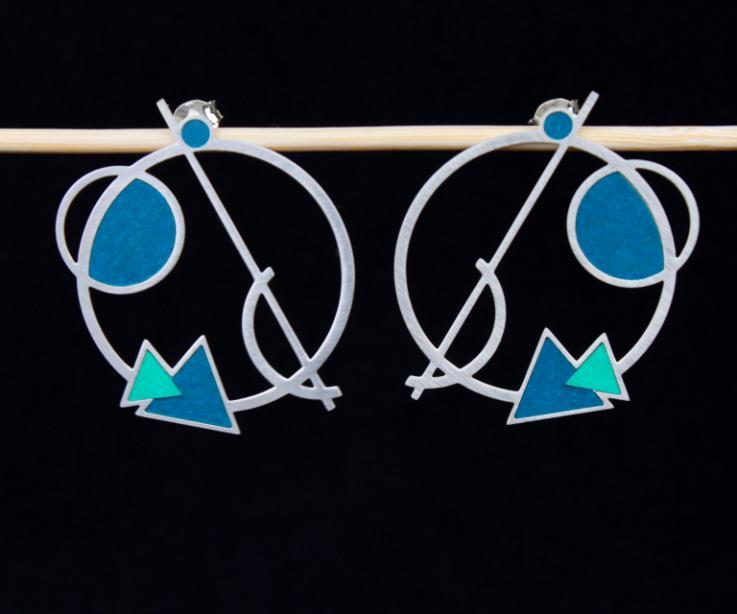 Plano frontal de dos zarcillos plateados con base troquelada y formas geométricas superpuestas con engastes de papel en tonos coordinados de turquesa.