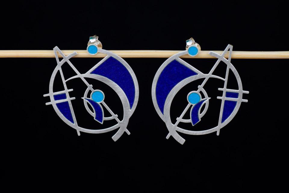 Originales aretes plateados con base de aro troquelado y diseño de formas geométricas con círculos, engastes de papel cobalto y azul, y cierre de tuerca.