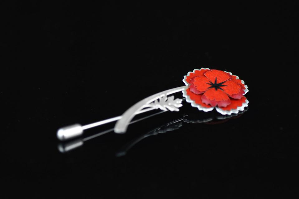 View detail of brooch with pin closure and a red poppy paper with gloss finish that mounts on a metal base carved in the shape of a flower.