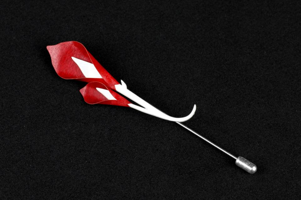 Silver-plated and carved pin in a single piece with stems ending in red-set paper, modelled on two gannet flowers.