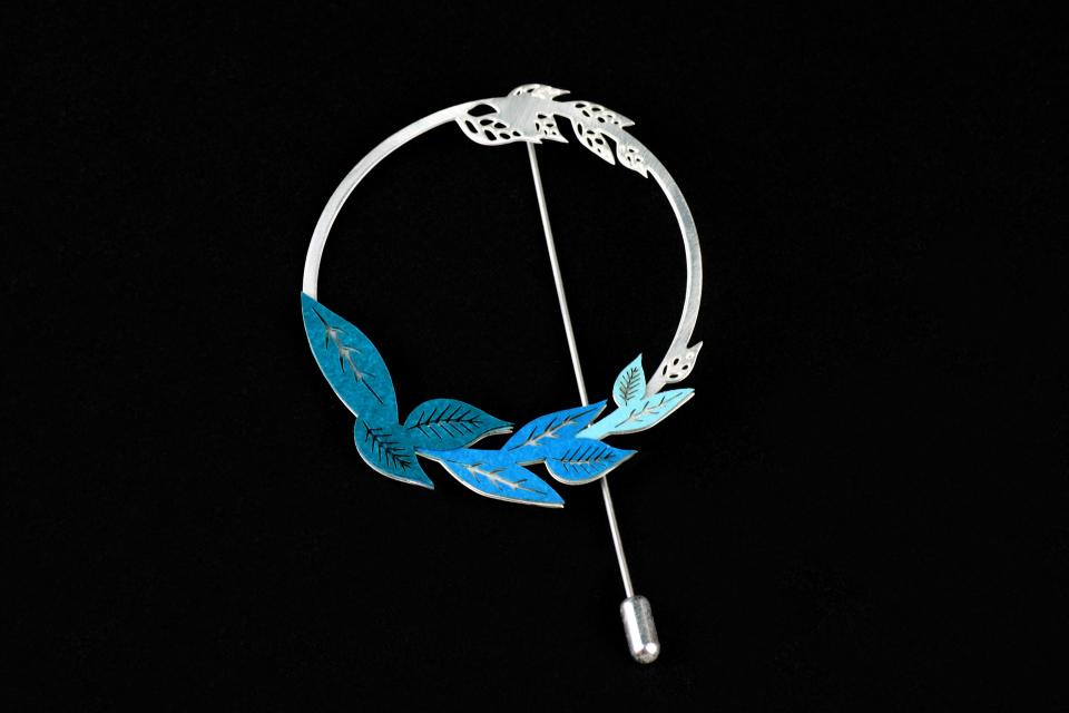 Silver brooch with modeled paper, needle lock, and a circular base with filigree branches carved in the same piece and blue leaf details.