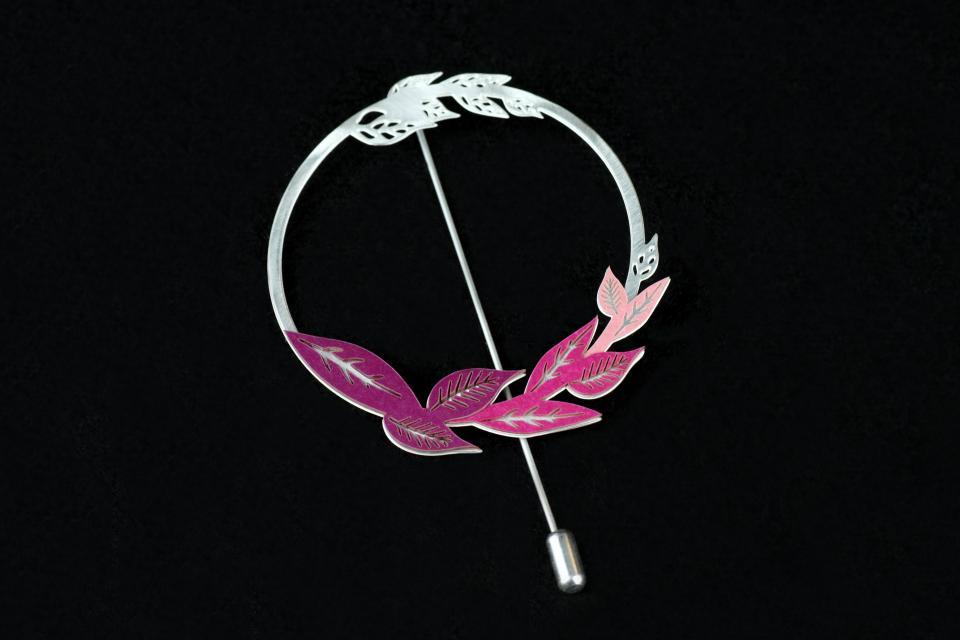 Vista frontal de prendedor circular argentado con agujón, pequeñas hojas talladas en la misma pieza y hojuelas de papel de tonos rosados y morados.