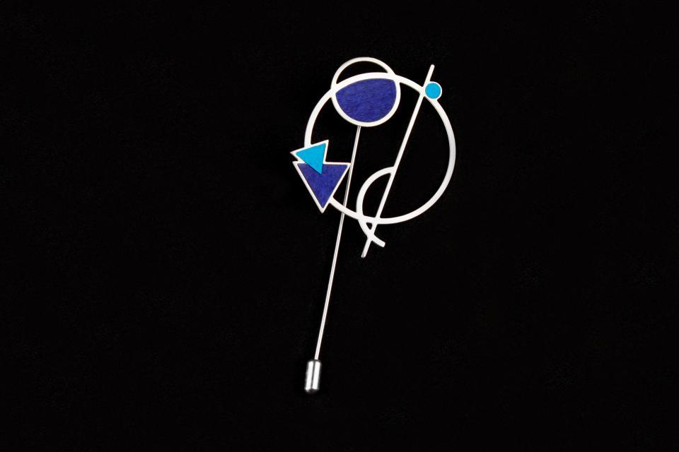 Prendedor de aguja con formas geométricas vaciadas sobre una única estructura plateada y adornada con pequeños vivos de papel coordinados en color azul.