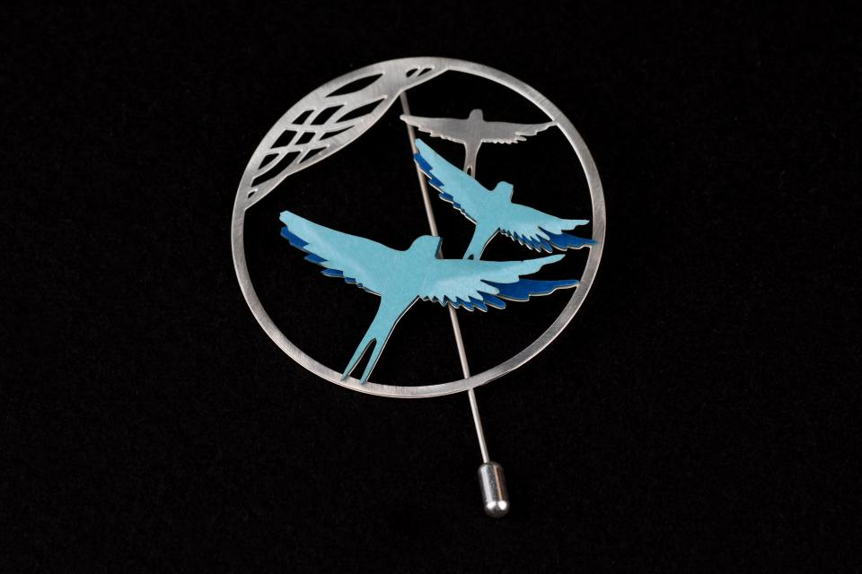 Silver brooch with circular base, filigree and bird silhouettes with blue-toned paper layer setting with 3D effect and needle lock.