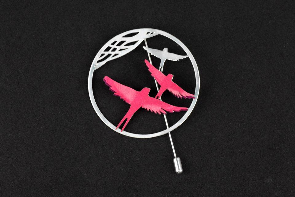 Broche plateado con base circular, cierre de aguja, filigrana y engastes de pájaros de papel con alas semi desplegadas de tonos rosados.