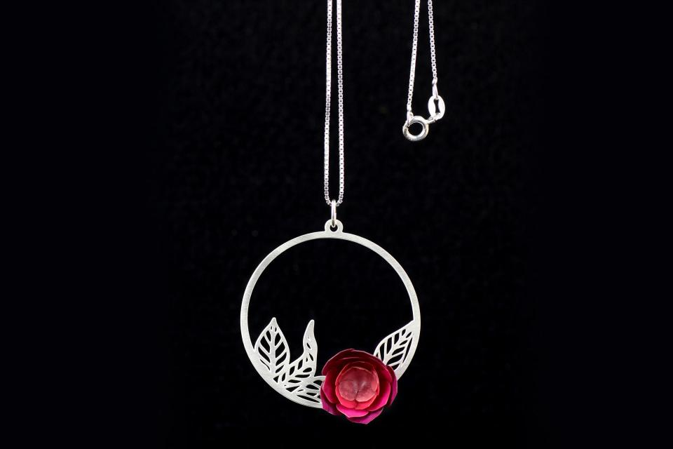 Frontal shot of a carved pendant with a pink paper camellia flower mounted on a filigree leaves ring and attached to a silver chain