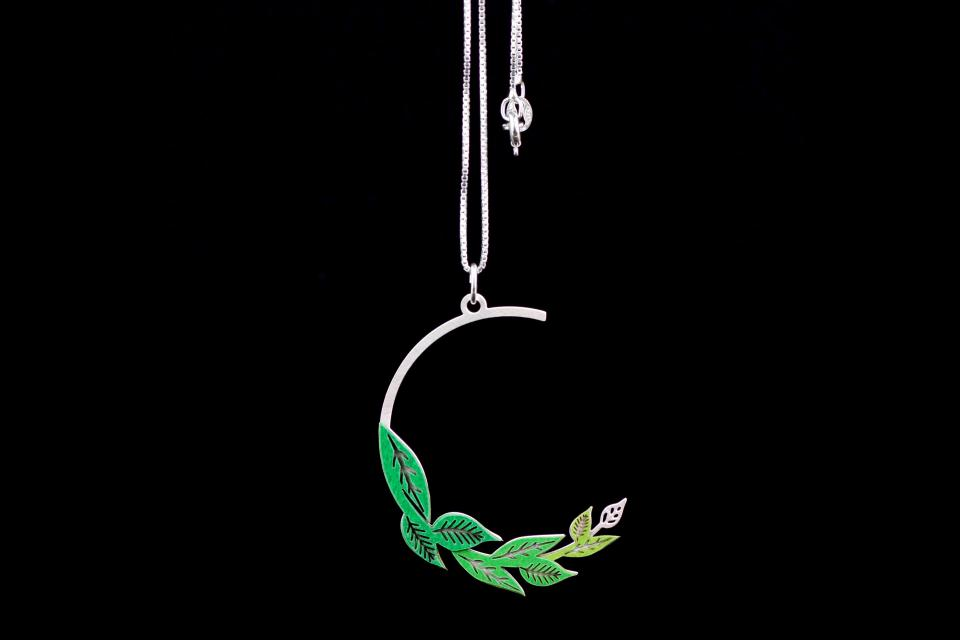 Front view of pendant with inlaid green paper leaves on a semi-circle with carved branches and fine silver chain.