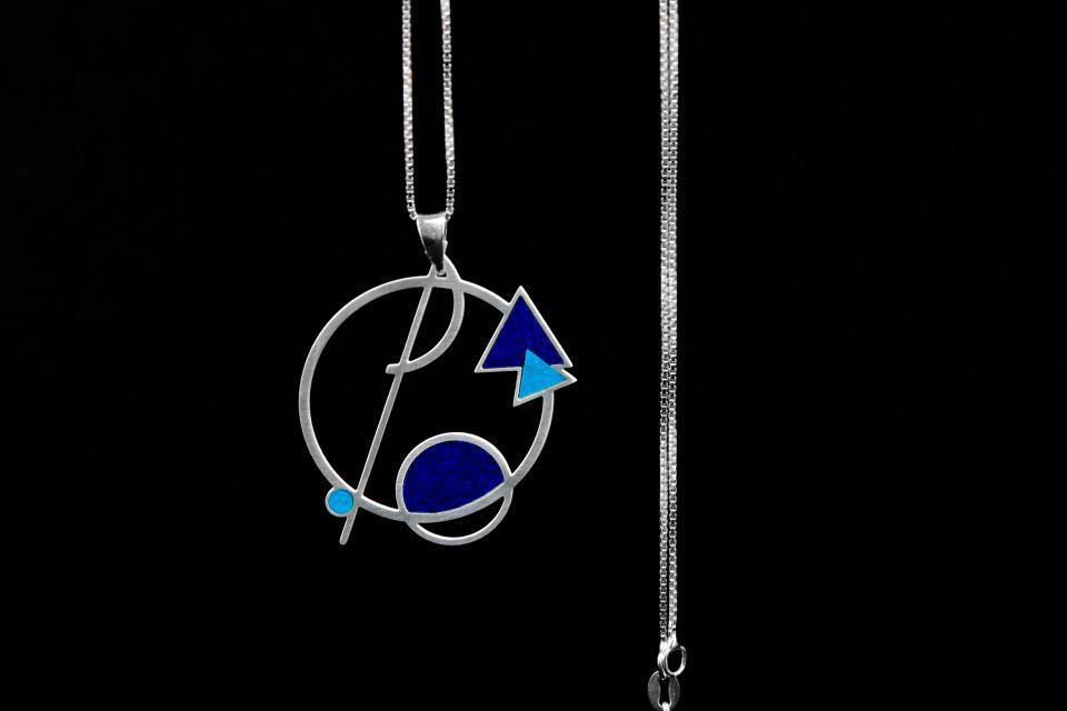 Primer plano de colgante circular de inspiración geométrica vaciado con líneas, triángulos y círculos, con engastes de papel azul y cadena plateada.