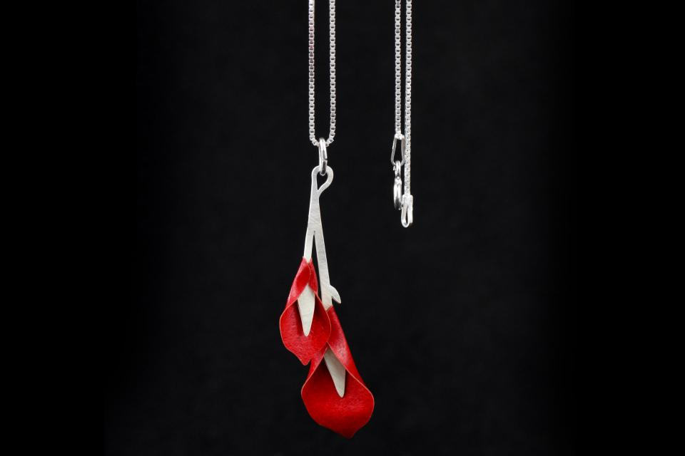 Close-up of silver pendant, with carmine paper gannet flowers and stems on a chiseled base attached to a fine silver chain.