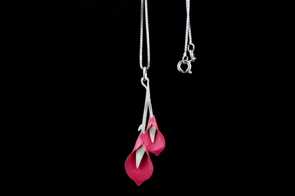 Detail shot of pendant with lillium flowers modelled on bright pink paper that are set on a sterling silver Venetian chain.
