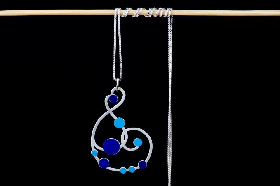 Vista frontal de un collar plateado formado por cadena fina y un hermoso colgante de formas sinuosas embellecido con engarces de papel en tonos celúreos.