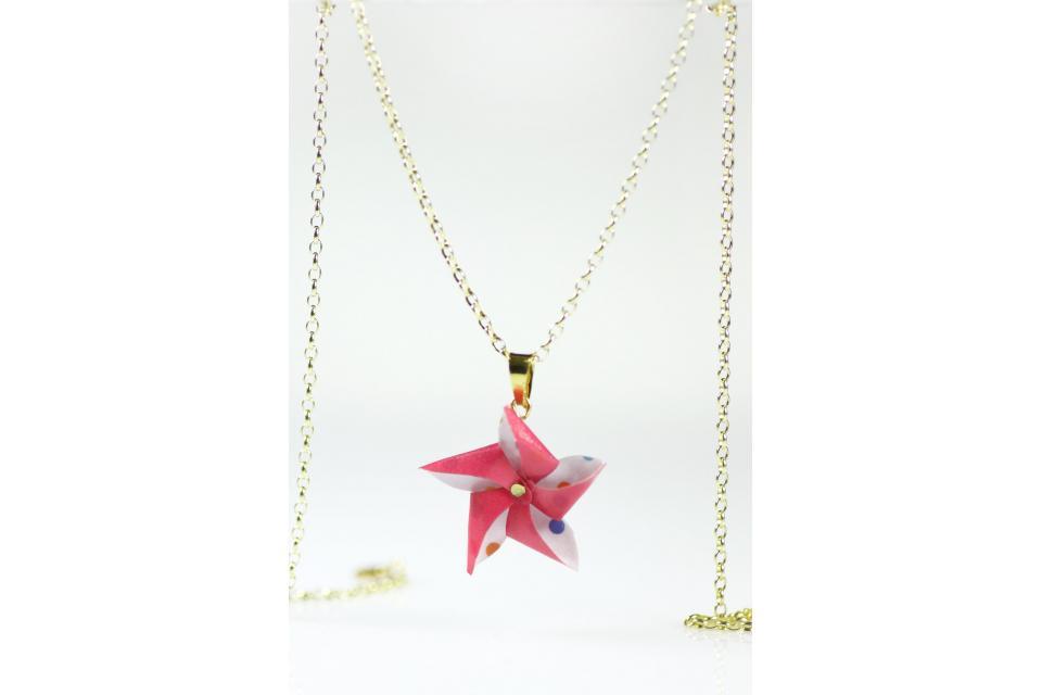 Golden pendant and handmade paper pinwheel, front view