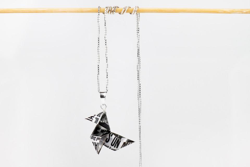 Vista frontal sobre fondo blanco de colgante con dije en forma de pajarita de papel de periódico antiguo con acabado semi brillo y cadena fina de plata.