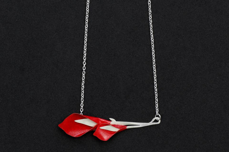 Close-up of pendant with two red paper gannet flowers set to a horizontal base of die-cut branches with silver chain.