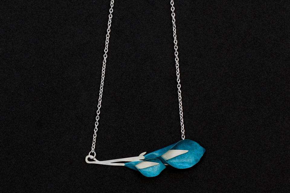 Close-up of a necklace with gannet flowers on blue-green paper, set on a horizontal base of die-cut branches with a silver chain.