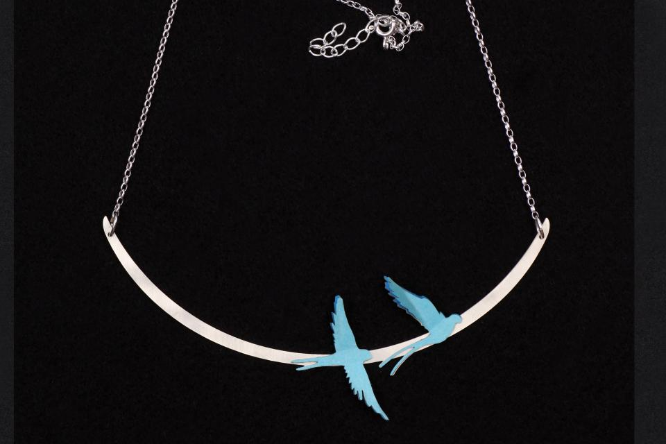 Silver-plated necklace with two birds made of treated paper in layers of blue tones, mounted on a fine semi-ellipse attached to a chain of links.