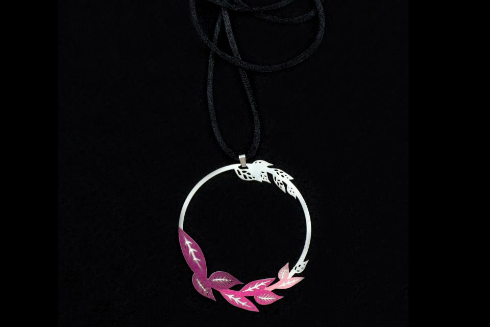 Close-up of pendant with mauve paper leaves inlay on a hoop with black cord.