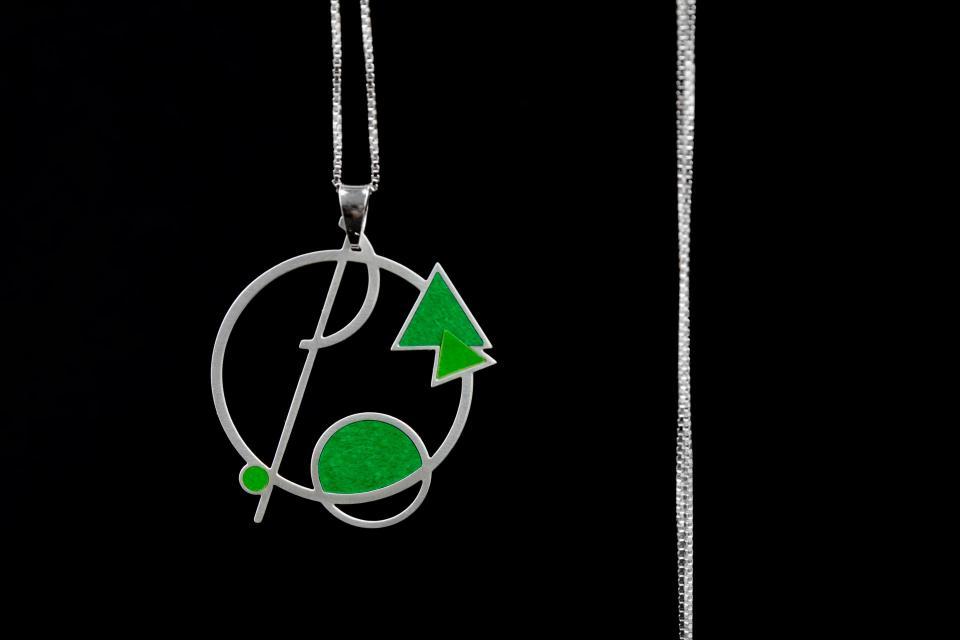 Colgante con base circular de color plata y composición geométrica abstracta con engastes de papel verde semi brillo, engastado a cadena fina y larga.