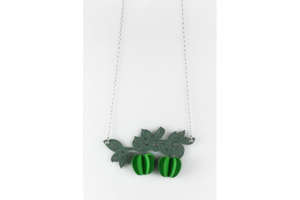 Jewellery in the shape of branches decorated with cheerful green apples that evoke the popular work of the surrealist Magritte