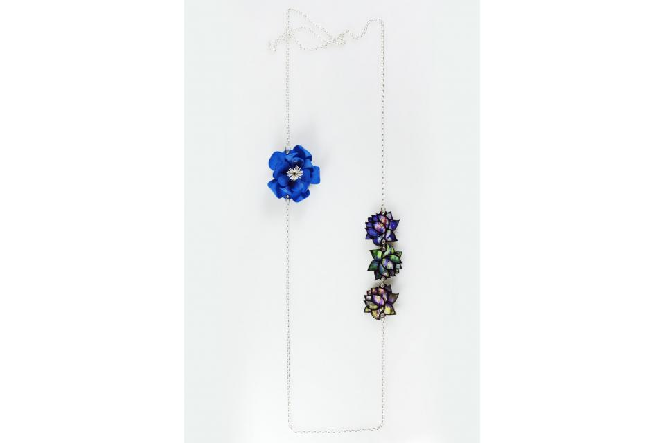 Long silver necklace with a blue flower and three flat flowers with the profile of a water lily