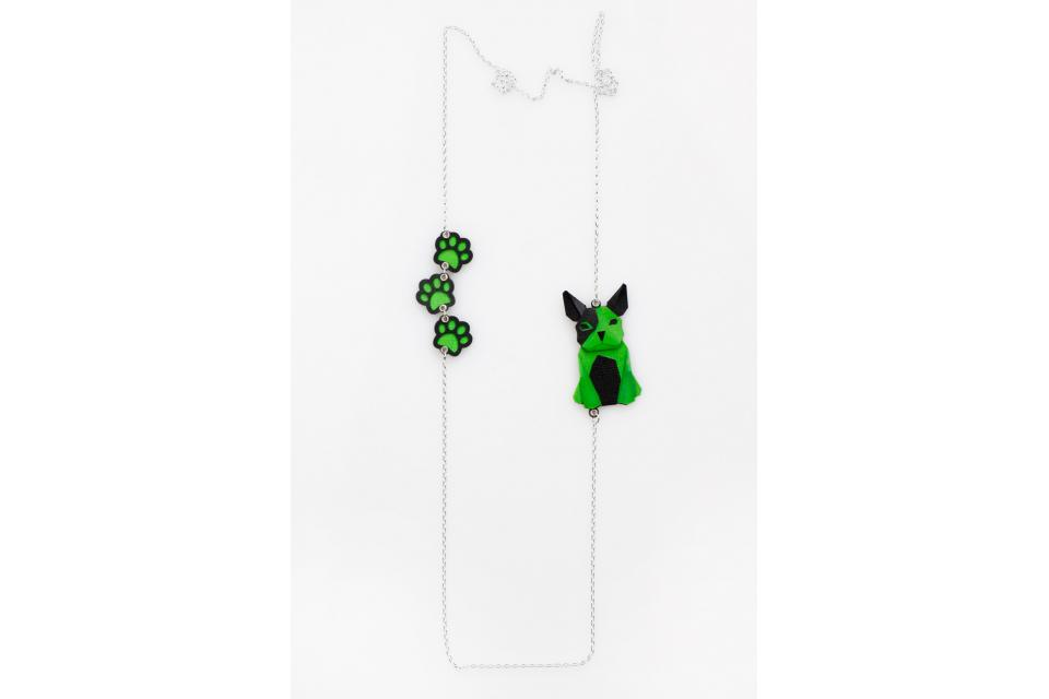 Silver necklace with a green origami dog and footprints