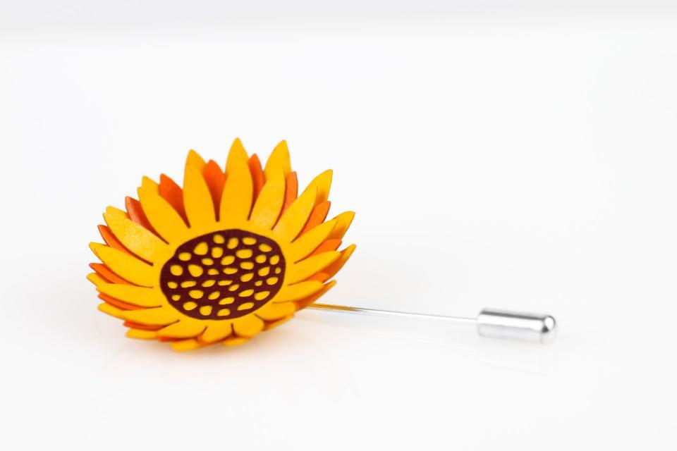 Prendedor de aguja plateado con una preciosa flor de girasol con efecto 3D elaborada con capas de papel endurecido en tonos amarillos y tostados.