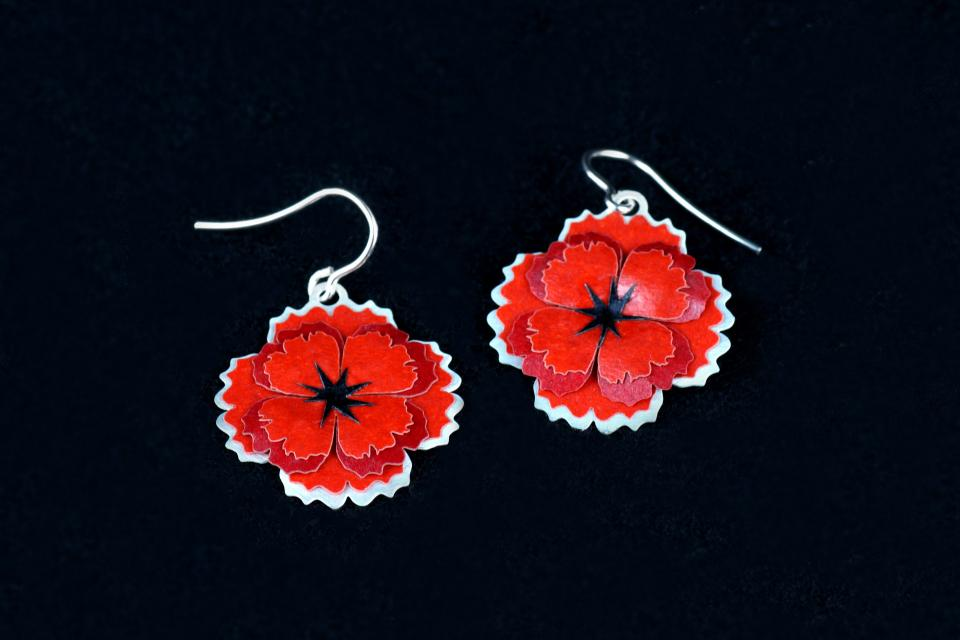 Front view of a pair of carved earrings, with silver hook closure and two handcrafted poppies made with carmine paper petals.