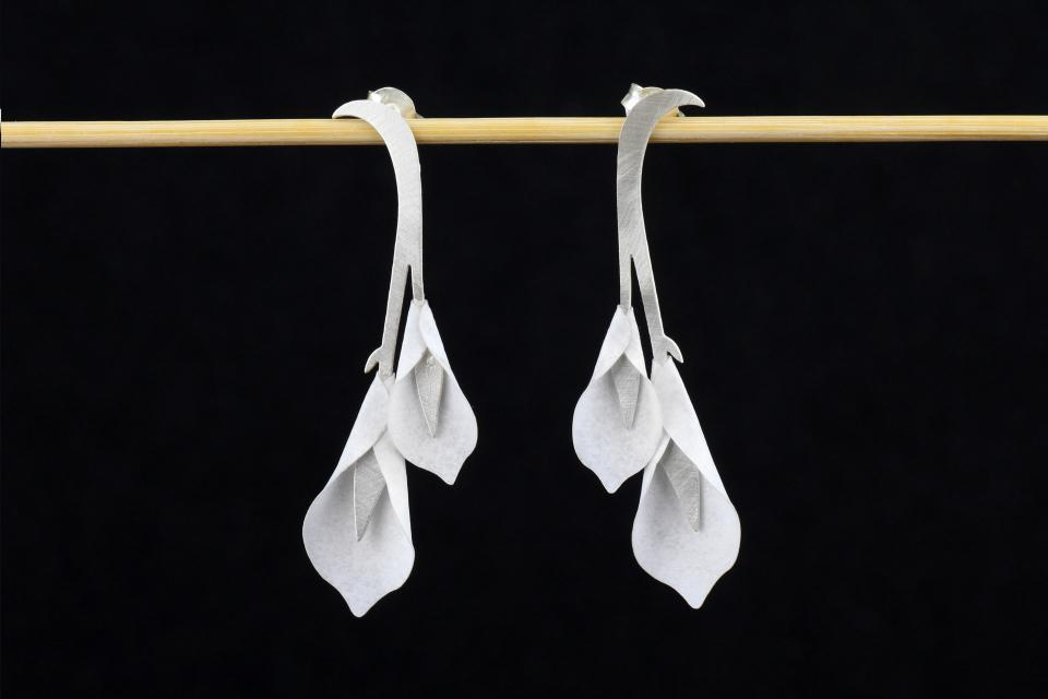Front view of two semi-long earrings with hidden silver clasp and inlaid white paper gannet flowers with semi-gloss finish.