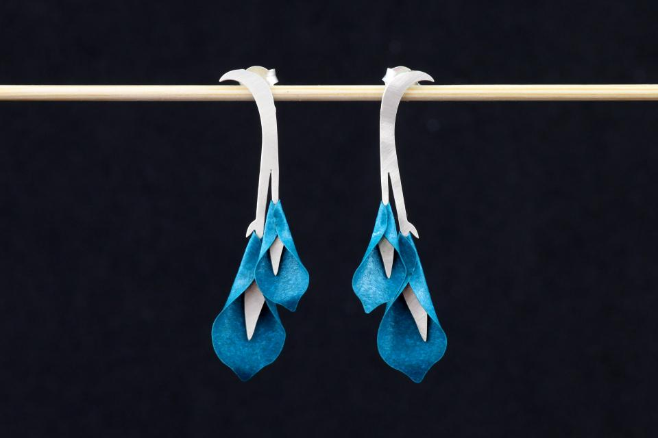 Front view of a pair of semi-long earrings, with silver snap fasteners and lilies set with special paper petals in aquamarine tones.