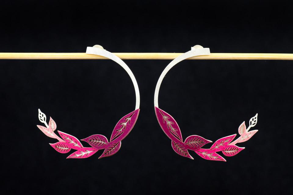 Front view of two earrings, with hidden closure and carved sections with die-cut leaf settings and set in mauve paper.