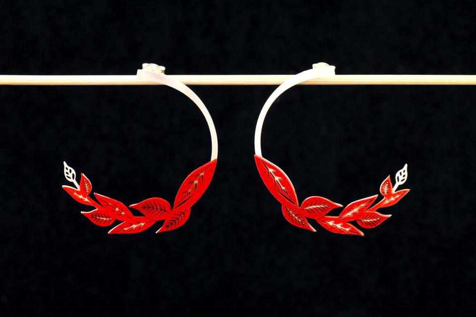 Front view of two carved earrings, with hidden silver clasp and sections with die-cut leaf settings and set in carmine paper.