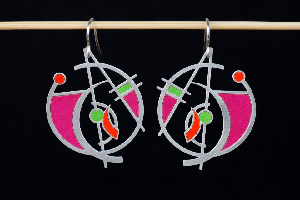 Vista frontal de zarcillos circulares plateados con diseño de líneas, cuadrados y aros, vivos de papel de color morado, lima y rojo y cierres tipo gancho.