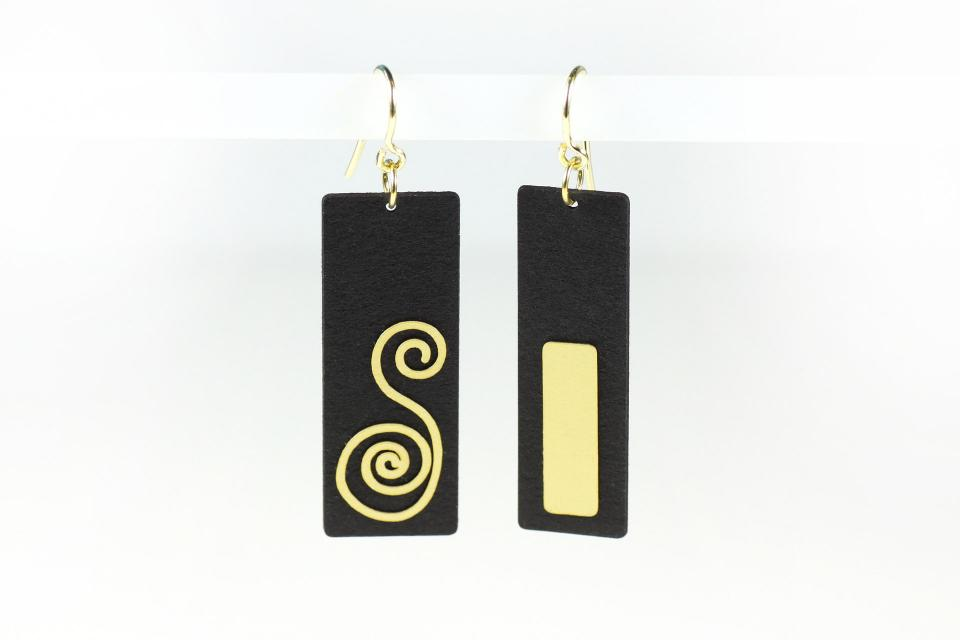 Earrings of black paper treated and set in gold-plated silver.