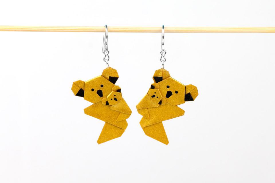 Simpáticos koalas de origami plegados a partir de un único cuadrado de papel en colores dorados con acabados metalizados y acabados en plata de ley.
