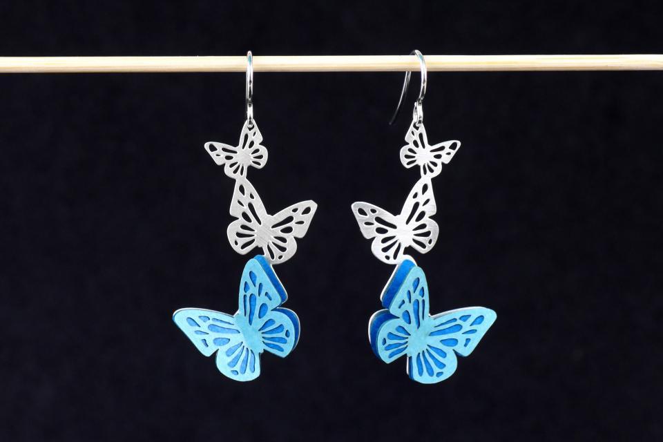 Un par de zarcillos plateados, con mariposas talladas en la base, engastes de pequeñas alas de papel de tonos azules, y finos cierres de gancho en plata.