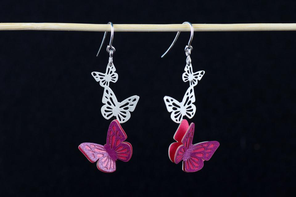 Front view of two earrings with silver hook closure and three butterflies carved in one piece, with mauve hardened paper wings.