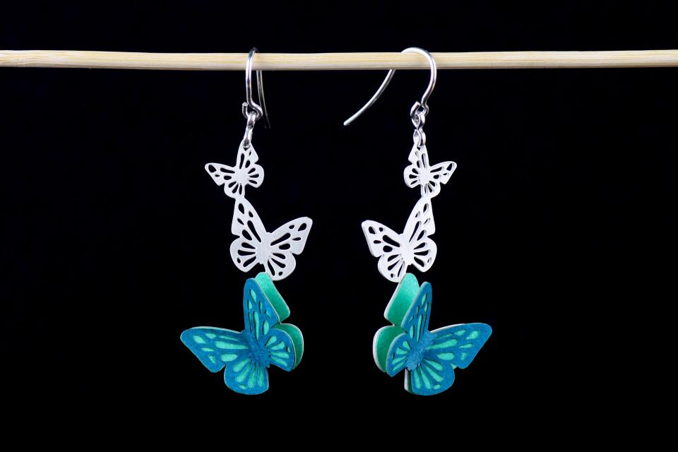 Frontal view of a pair of silver-plated and carved pieces with elegant blue-green paper 3D butterflies, die-cut and partially overlapped.