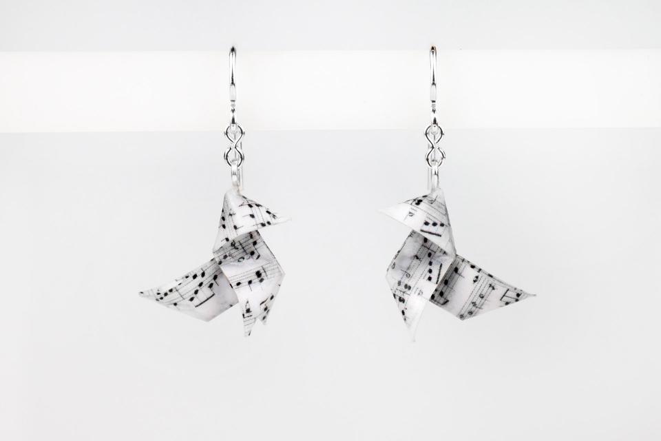Vista frontal de un par de elegantes zarcillos con engastes de pajaritas elaboradas con partituras de papel plegado y cierres de gancho en plata.