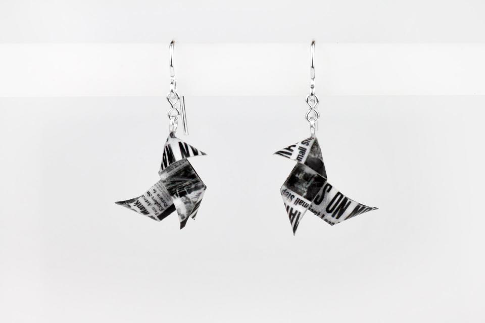 Vista frontal de zarcillos con forma de pajaritas de papel de periódico antiguo, con acabado semi brillo y engarzados a cierres de plata tipo gancho.