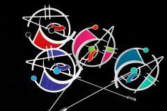 Set de cuatro originales alfileres de inspiración geométrica embellecidos con pequeños engastes de papel de colores brillantes sobre un fondo negro.