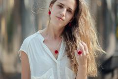 Woman with rose ring, rose pendant and rose earrings, all made of paper and silver