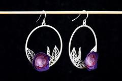 Earrings with silver clasps, carved leaves at the base and camellias made with petals modeled on paper with purple tones with gloss lacquer.
