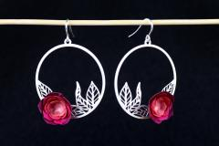 Frontal view of a pair of hoop earrings, with carved leaves and elegant pink hardened paper camellias with semi-gloss finish.