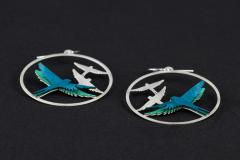 Two silver hoop earrings with carved flock and detail of the paper layers superimposed with 3D effect that shape the turquoise birds.