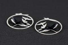 Detail view of two earrings with black paper birds mounted in layers with 3D effect on a circular carved base, and hook closures in unfocused plane.